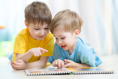 Photo for Kids brothers practice reading together looking at book laying on the floor - Royalty Free Image