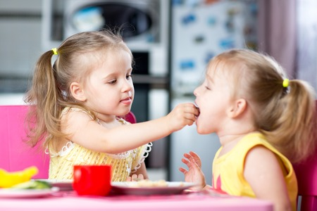 Foto de Two little children toddlers eating meal together, one girl feeding sister in sunny kitchen at home - Imagen libre de derechos
