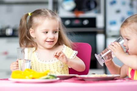 Photo for Cute little children drinking water at daycare or nursery - Royalty Free Image