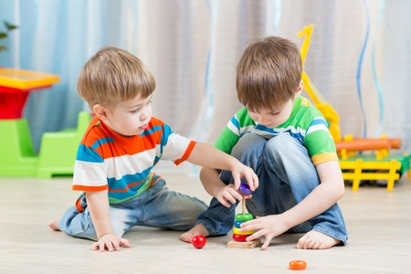 Foto de little children boys playing with toys at home - Imagen libre de derechos