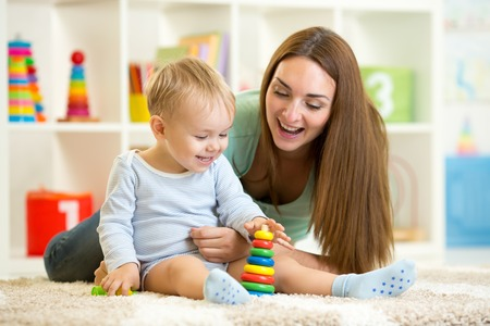 Foto de little child boy and his mommy play with toys at home - Imagen libre de derechos