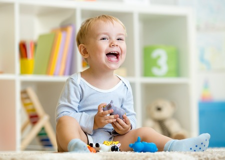 Foto de Happy little boy. Smiling child toddler plays animal toys at home or kindergarten. - Imagen libre de derechos