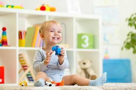 Foto de happy child boy holds elefant toy sitting on floor in nursery - Imagen libre de derechos