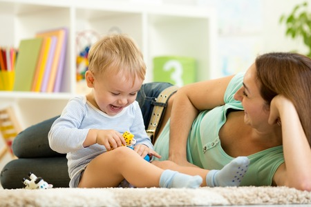 Foto de happy child boy holds animal toy playing with mom in nursery - Imagen libre de derechos