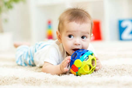 Photo for cute baby lying on soft carpet in children room - Royalty Free Image