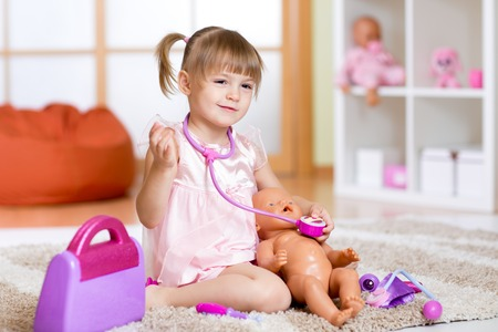 Photo for Little girl plays doctor examining baby doll patient with toy stethoscope - Royalty Free Image