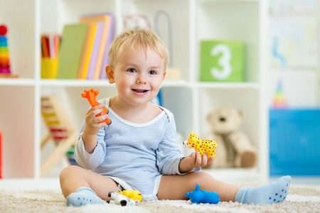 Foto de smart child boy plays animal toys sitting on floor - Imagen libre de derechos