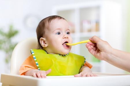 Photo pour mother feeding baby girl at home kitchen - image libre de droit