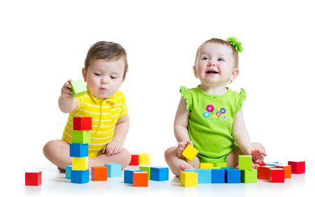 Foto de Two adorable babies kids playing with educational toys. Toddlers girl and boy sitting on floor. Isolated on white background. - Imagen libre de derechos