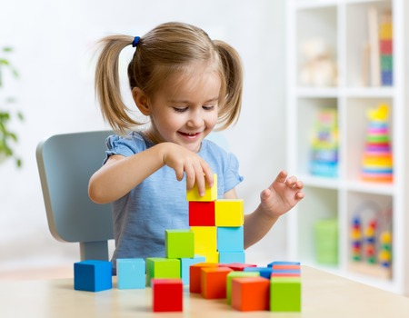 Foto de child little girl playing wooden toys at home or kindergarten - Imagen libre de derechos