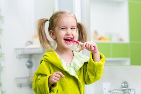 Photo pour Smiling child kid girl brushing teeth in bathroom - image libre de droit
