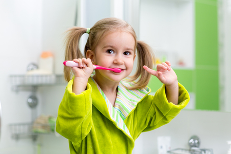Photo pour Smiling kid child girl brushing teeth in bathroom - image libre de droit