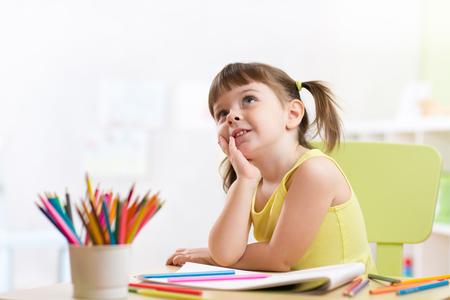 Foto de Cute dreamy kid girl drawing with color pencils in nursery - Imagen libre de derechos