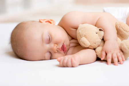 Foto de Carefree sleep baby boy with soft toy on bed - Imagen libre de derechos