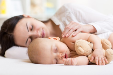 Foto de beautiful woman and her son little baby sleeping together in a bedroom - Imagen libre de derechos