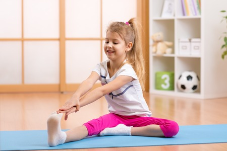 Photo pour Sportive kid girl doing gymnastic at home - image libre de droit