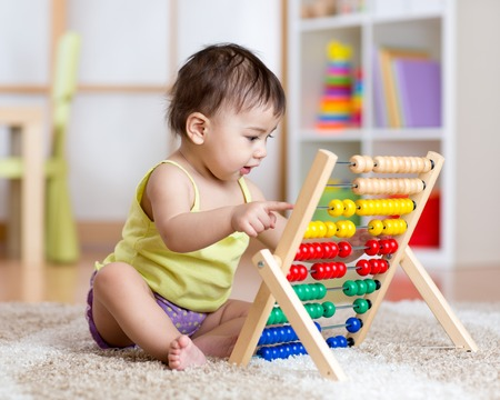 Foto de Cute baby boy playing with counter toy - Imagen libre de derechos