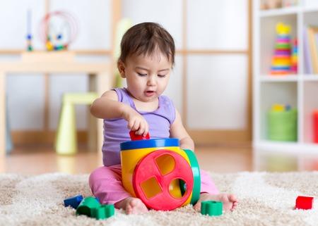 Foto de Cute toddler girl playing indoors with sorter toy sitting on soft carpet - Imagen libre de derechos