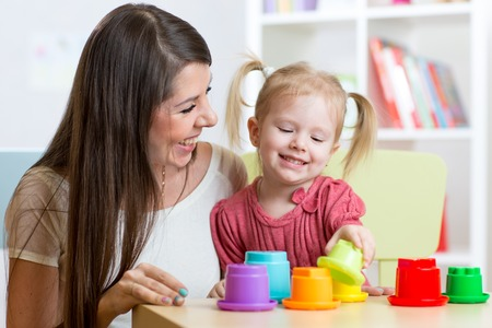 cute mother and her child play toys indoors
