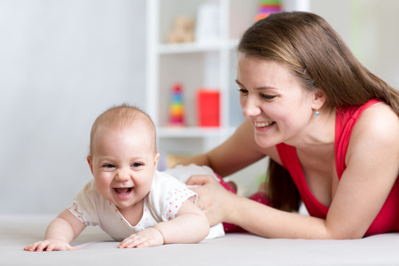 Photo pour Happy family. Mother and baby playing, laughing and hugging - image libre de droit