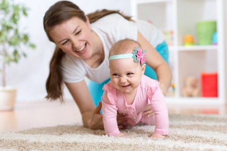 Photo pour Funny crawling baby girl with mother at home - image libre de droit