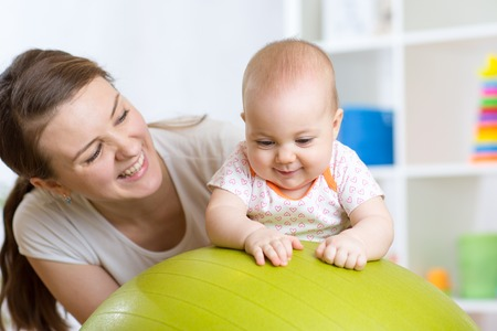 Foto für Mother with happy child doing exercises with green gymnastic ball at home. Concept of caring for the baby's health. - Lizenzfreies Bild