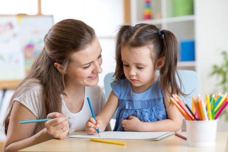 Photo pour Young mother looking how her child daughter drawing a picture - image libre de droit