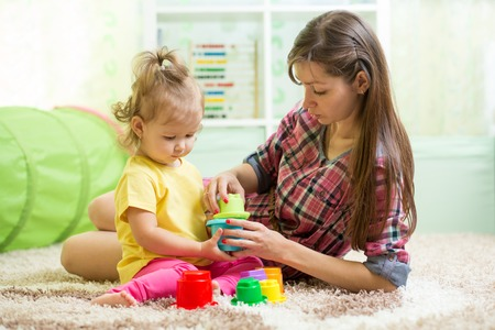 Foto de babysitter with kid girl playing in nursery - Imagen libre de derechos