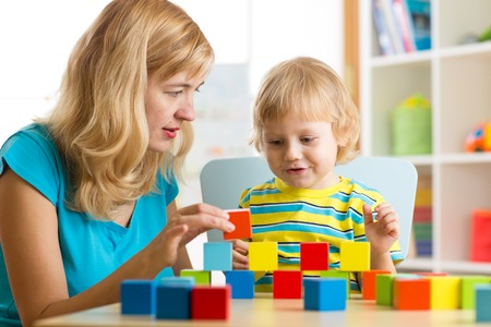 Foto de Child boy together with mother playing educational toys - Imagen libre de derechos