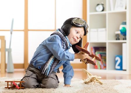 Photo pour Children dreams concept. Adorable little boy playing with wooden airplane - image libre de droit