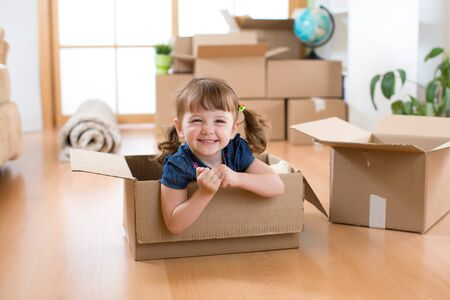 Photo for Laughing little girl sitting in cardboard boxe in her new home - Royalty Free Image