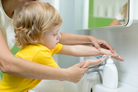 Foto de Mother and kid son washing their hands in the bathroom. Care and concern for children. - Imagen libre de derechos