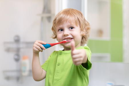 Photo pour Little boy brushing his teeth in the bathroom. Smiling child holding toothbrush and showing thumbs up. - image libre de droit