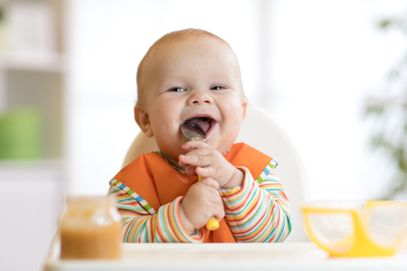 Photo pour Cheerful baby child eats food itself with spoon. Portrait of happy kid boy in high-chair. - image libre de droit