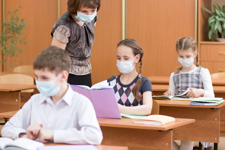 Photo pour school children with protection masks against flu virus at lesson in classroom - image libre de droit