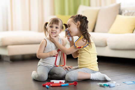 Photo pour Two happy children, cute toddler girl and her older kid sister, playing doctor and hospital using stethoscope toy and other medical toys, having fun at home - image libre de droit