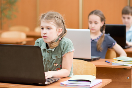 Photo for Group of elementary school children working together in computer class at laptop - Royalty Free Image