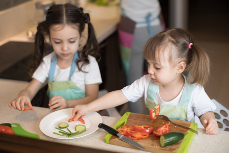 Photo for Cute children helping mother at kitchen. Adorable kids sisters making funny face with vegetables on plate. - Royalty Free Image