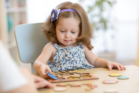 Foto de Small toddler or baby kid playing with puzzle shapes on low table in children room in nursery or preschool. - Imagen libre de derechos