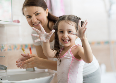 Photo pour Pretty woman and daughter child girl washing hands with soap in bathroom - image libre de droit