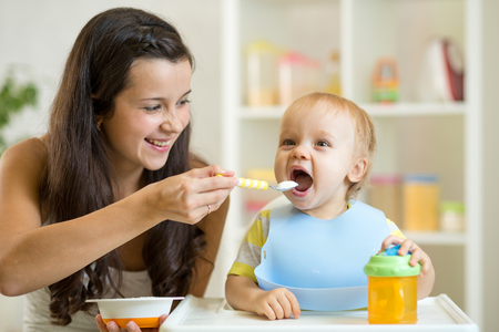 Photo pour Mother feeding her baby son with spoon. Mother giving healthy food to her adorable child at home - image libre de droit