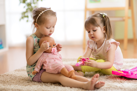 Foto de children playing doctor with doll indoor - Imagen libre de derechos