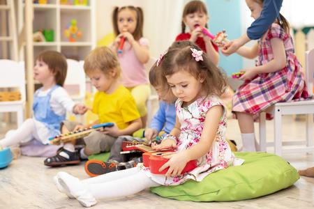 Foto de Children learning musical instruments on lesson in kindergarten - Imagen libre de derechos