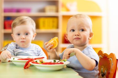 Photo pour Babies have a lunch in nursery - image libre de droit