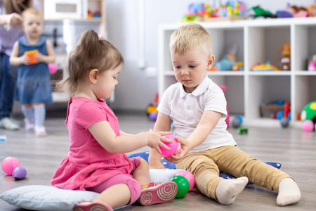 Foto de Little toddlers boy and a girl playing together in nursery room. Preschool children in day care centre - Imagen libre de derechos