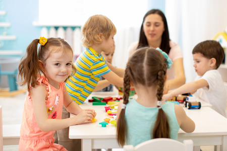 Photo pour Cute woman and kids playing educational toys at kindergarten or nursery room - image libre de droit