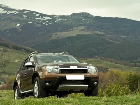 Photo pour Off road toursim adventure with a 4x4 car parked on a sloped meadow in the mountain - image libre de droit