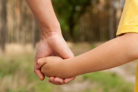 Photo for Mother holding a hand of his son in summer day outdoors - Royalty Free Image