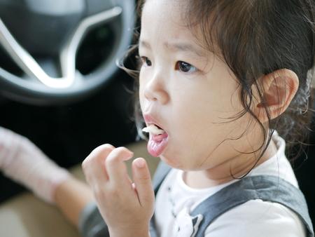 Foto de Little Asian baby girl, 24 months old, is choking while eating a piece of apple - Imagen libre de derechos