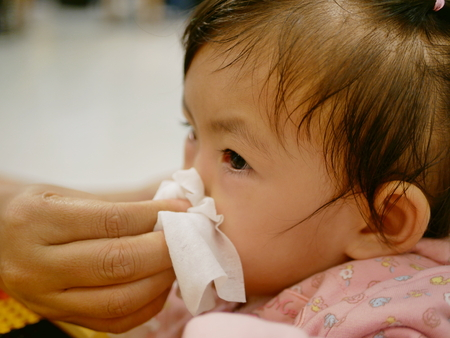 Foto für Close up of a mother hand squeezing her daughter running nose - cleanning a baby's stuffy nose - Lizenzfreies Bild